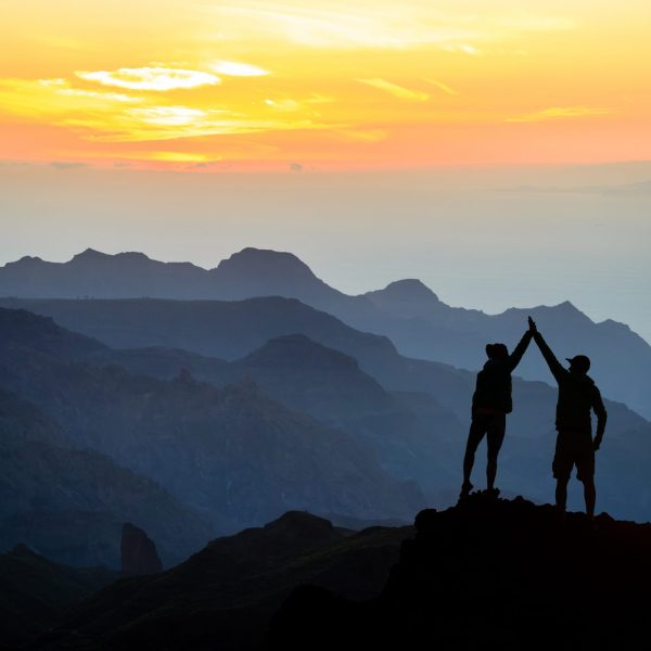 Teamwork couple helping hand trust help, silhouette success in mountains. Team of climbers man and woman. Hikers celebrate with hands up, help each other on top of mountain, sunset landscape.